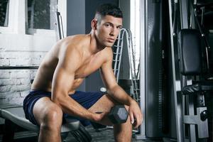 uomo muscoloso allenamento con manubri in palestra foto