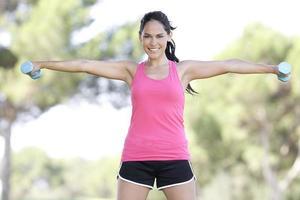 pesi fitness ragazza di sollevamento all'aperto