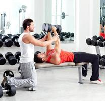 palestra personal trainer uomo con allenamento con i pesi foto
