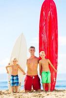 padre e figli che vanno a fare surf foto
