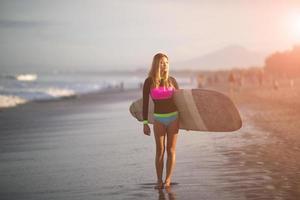 la ragazza con il surf all'alba foto