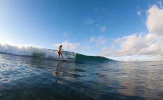 la ragazza con il surf all'alba. foto