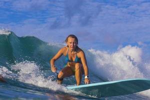 ragazza surfista sulla straordinaria onda blu foto