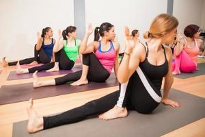 torcendo la posa prudente nella lezione di yoga foto