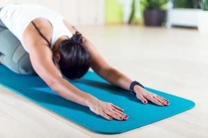 la donna adatta che fa l'allungamento dei pilates si esercita nello studio di forma fisica foto