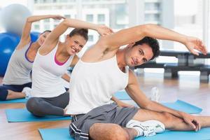 sportivi che allungano le mani a lezione di yoga foto