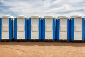 fila di bagni pubblici portatili in strada foto