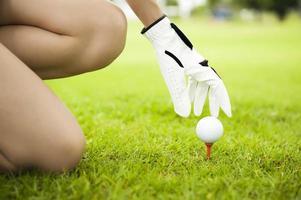 signora mano mettendo la pallina da golf sul tee foto