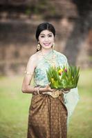 signora tailandese con cesto galleggiante per loi krathong festival. foto