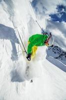 sciatore che scia in discesa in alta montagna foto