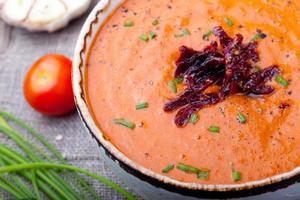 zuppa di pomodoro con pomodori secchi. fondo in legno