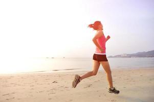 donna che corre sulla spiaggia foto