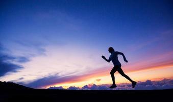 sagoma corridore femminile, correndo verso il tramonto foto