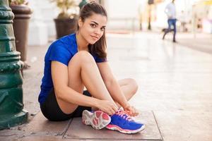 corridore latino legando le scarpe foto