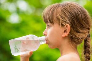 bambino che beve acqua di rubinetto pulita da una bottiglia di plastica trasparente foto