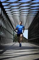 giovane uomo atletico praticando la corsa sportiva attraversando il ponte urbano della città foto
