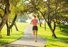 giovane donna che pareggia che corre all'aperto foto