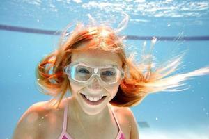 giovane donna dai capelli rossi che sorride sott'acqua con gli occhiali