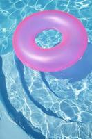anello rosa che galleggia in una piscina blu foto