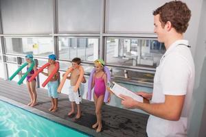 allenatore di nuoto con i suoi studenti a bordo piscina foto