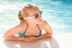 bella ragazza bionda con gli occhiali da sole nella piscina all'aperto foto