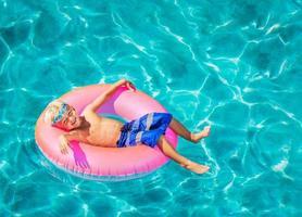 ragazzino divertirsi in piscina foto