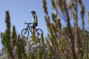 ciclista in mountain-bike maschio che si siede sulla bicicletta, fuoco sul fondo foto