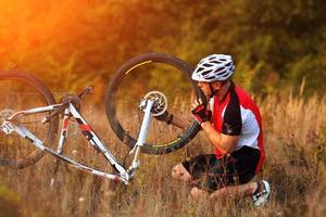 uomo che ripara la sua mountain bike foto