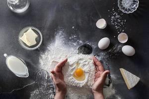 le mani della donna impastano la pasta sul tavolo con la farina foto