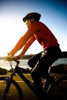 uomo in bicicletta durante il tramonto foto