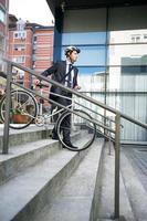 uomo d'affari attraente con la sua bici foto