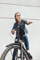 pantaloni a vita bassa della giovane donna che stanno con la bici nera