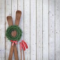 vecchi sci di legno sul muro di assi di legno con ghirlanda foto