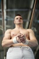 atleta in topless si prepara a dare esercizi ginnici sull'une