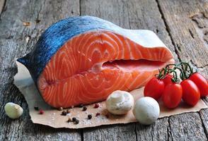 trancio di salmone crudo con pomodorini, funghi, cipolle, aneto, aglio foto