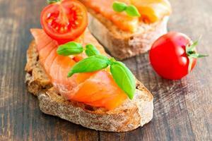 panino al salmone sul tavolo di legno con pomodoro foto