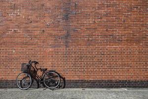 la bicicletta è attaccata con sfondo di mattoni