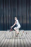 giovane donna in bicicletta con una macchina fotografica foto