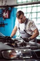 meccanico di auto con chiave inglese foto