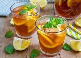 rinfrescante tè freddo al limone fatto in casa su un tavolo di legno foto