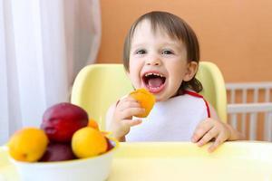 bambino sorridente che mangia frutta foto