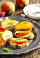 crostini con crema di formaggio e pesche fresche. foto
