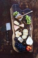 set di antipasti di vino: selezione di formaggi francesi, nido d'ape, uva, pesca e foto