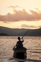 uomo Pagaiando una canoa tradizionale foto