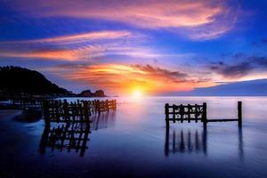 vista sul mare con fila di legno al tramonto