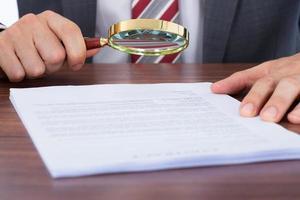 documento d'esame dell'uomo d'affari con la lente d'ingrandimento foto