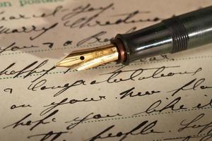 vecchia cartolina e penna stilografica vintage con pennino in oro foto
