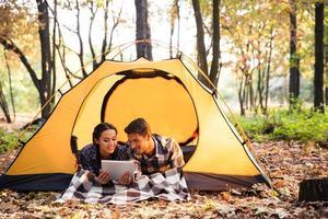 Ritratto di una coppia sorridente utilizzando il computer tablet foto
