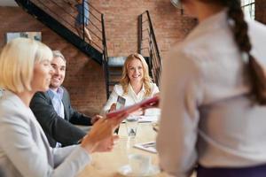 ambiziosi uomini d'affari riuniti al tavolo della sala riunioni discutendo foto