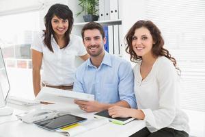 colleghe sorridenti che lavorano insieme alla scrivania foto